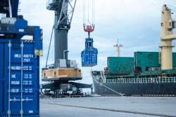 Кран переносит контейнер с удобрениями